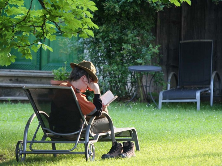 Gast liest im Garten